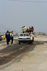 Members of the Iraqi police force man a permanent Vehicle Checkpoint or VCP stopping and checking cars, Vans, trucks and wagons on one of the busy roads in the Basra area of southern Iraq. March 2005