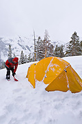 Backcountry skier and yellow dome tent,  Ansel Adams Wilderness, Sierra Nevada Mountains, California USA