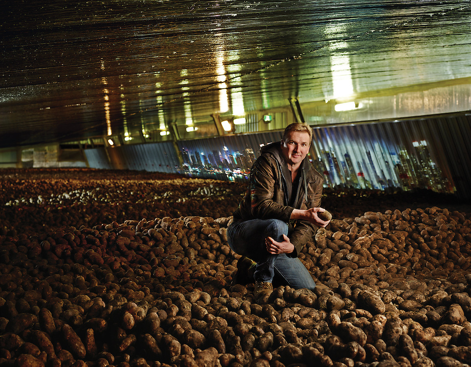 Potato farmer on top of 20 feet of potatoes from their harvest Shot on a PhaseOne IQ180 as a Environmental Portrait.