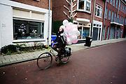 In Utrecht fietst een vrouw met ballonnen door de stad.<br /> <br /> In Utrecht a woman cycles with balloons.