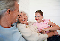 Senior woman hugging granddaughter with senior man sitting in weatherboard room