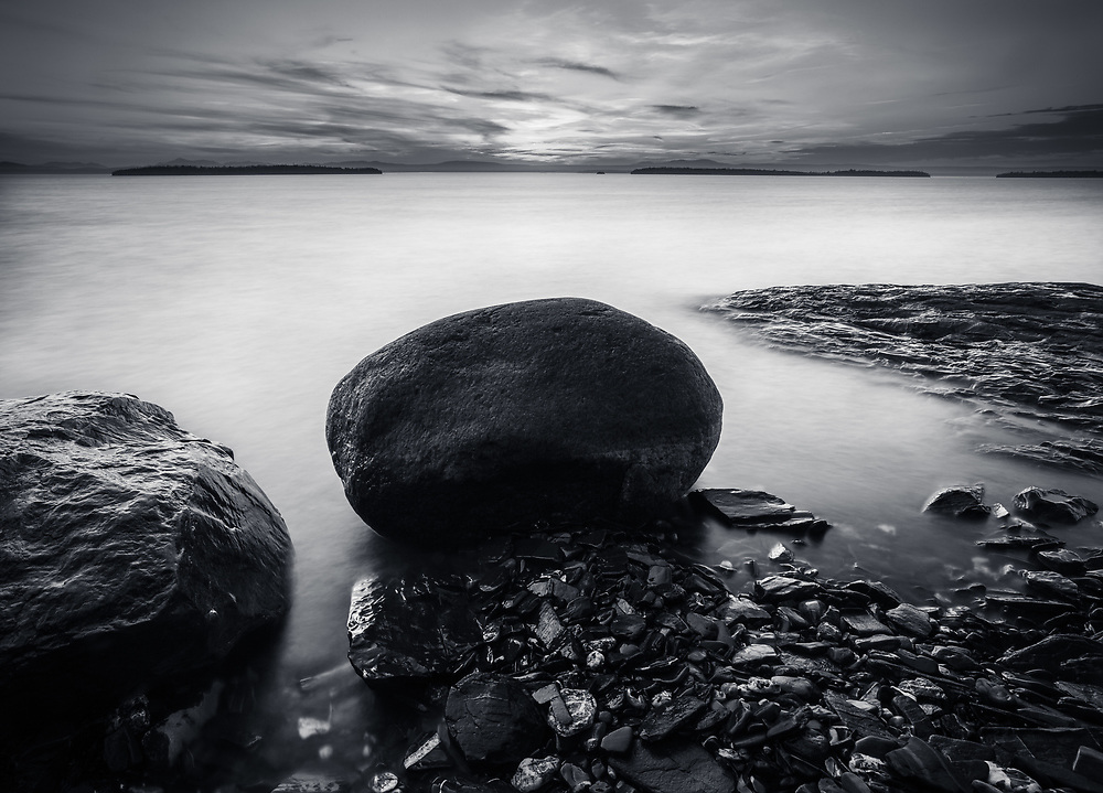 Long exposure black and white image of boulders along the shore of Lake Champlain in South Hero, Vermont
