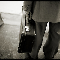 Male figure carrying suitcase outdoors