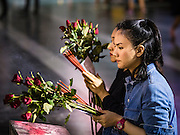 18 FEBRUARY 2016 - BANGKOK, THAILAND: Women pray, holding nine red roses and sticks of incense, at the Trimurti Shrine in Bangkok. Every Thursday night, starting just after sunset and peaking at 21.30, hundreds of Bangkok single people, or couples seeking guidance and validation, come to the Trimurti Shrine at the northeast corner of Central World, a large Bangkok shopping mall, to pray to Lord Trimurti, who represents the trinity of Hindu gods - Brahma, Vishnu and Shiva. Worshippers normally bring an offering of red flowers, fruits, one red candle and nine incense sticks. It's believed that Lord Trimurti descends from the heavens at 21.30 on Thursday to listen to people's prayers. Although most Thais are Buddhists, several Hindu traditions have been incorporated into modern Thai Buddhism, including reverance for Trimurti.       PHOTO BY JACK KURTZ
