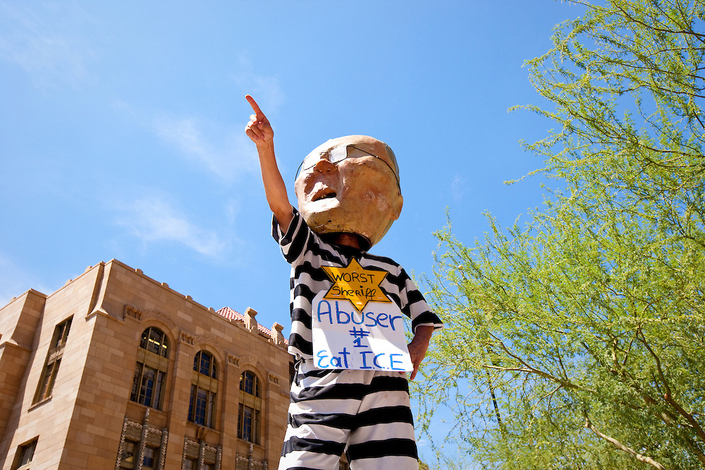 July 29, 2010. As SB1070, Arizona's Illegal immigration law take effect today, thousands of people protested in front of Sherif's Joe Arpaio's office, the US Courthouse, and the County Jail.  Over 3 dozens protesters were arrested after blocking the street and forming a human chain in front of the County Jail.///A protester wearing a prison uniform and a mask mimicking Sheriff Joe Arpaio is seen during the demonstration.