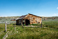 Old abandoned wooden barn with fence posts, surrounded by green grass and sage brush at Bodie State Historic Park in the eastern Sierra.