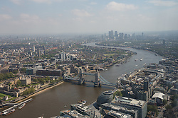 © Licensed to London News Pictures. 13/06/2016. LONDON, UK.  An aerial view of London showing Tower Bridge and the Canary Wharf financial district along the River Thames during sunny spring weather today. Haze and pollution is seen hanging towards the horizon.  Photo credit: Vickie Flores/LNP