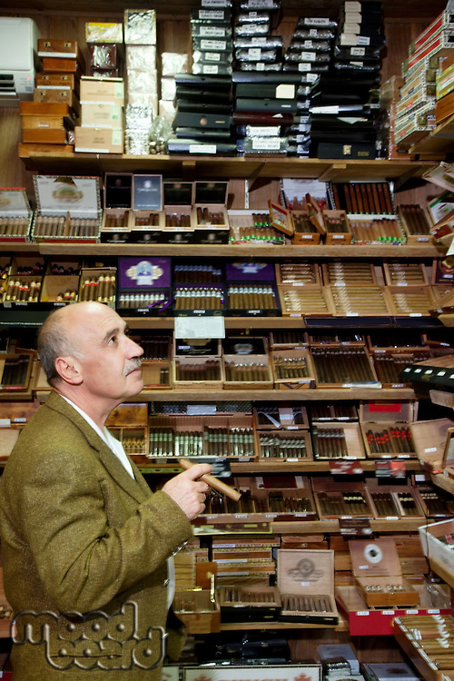 Mature tobacco shop owner looking at cigars on display