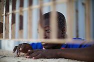 ITALY, Pozzallo - A young immigrant from Mali is portayed inside the temporary accomodation center in the port of POzzallo (Sicily).<br /> Pozzallo, Italia - 17 giugno 2014. Un giovane immigrato del Mali ritratto all'interno del centro di accoglienza aprovvisorio allestito all'interno del porto di Pozzallo in Sicilia. Sono migliaia gli immigrati giunti nelle ultime settimane in Sicilia che si trova a fronteggiare