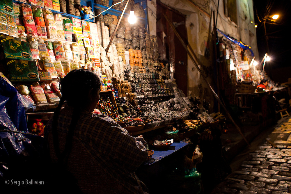 A vendor sells handicrafts to tourists in the Witches Market near Sagarnaga Street in La Paz, Bolivia.