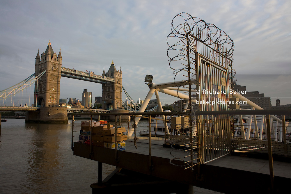 London's famous Tower Bridge with a secure jetty razor-wire and stacked boxes of new catering supplies on the River Thames.
