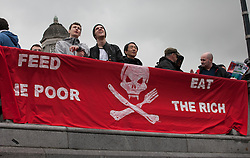 Occupy Wonga May Day. Protesters gather on the annual May Day march with a banner about poverty saying:'Feed the poor, Eat the rich' in Trafalgar Square, Central London, United Kingdom. Thursday, 1st May 2014. Picture by Daniel Leal-Olivas / i-Images