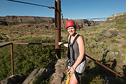 Woman smiling while zip lining with the Perrine Bridge beyond in the Snake River Canyon with Zip the Snake in Twin Falls, Idaho.