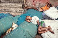 Fishermen sleeping on fishing nets with a dog in Mumbai's harbor.