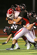 Washington's Charles Blades (7) is brought down by a group of Linn-Mar defenders during the first quarter of the game between Cedar Rapids Washington and Linn-Mar at Linn-Mar Stadium in Marion on Friday, September 14, 2012.