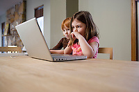 Two girls (5-6) at table using laptop