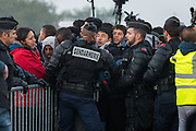 CALAIS, FRANCE - OCT 25: French riot police intervene to stop people pushing as a group of unaccompanied minors line up to register at a processing centre in the makeshift migrant camp known as 'the jungle' as its demolition begins in Calais, France on October 25, 2016.