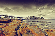 dramatic landscape of Bare Island with foot bridge and rocks in the foreground unader a story overcast sky