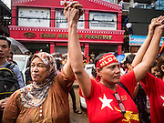 09 NOVEMBER 2015 - YANGON, MYANMAR:  A Muslim woman links hands with a Buddhist woman at NLD headquaters Monday. Thousands of National League for Democracy (NLD) supporters gathered at NLD headquarters on Shwegondaing Road in central Yangon to celebrate their apparent landslide victory in Myanmar's national elections that took place Sunday. The announcement of official results was delayed repeatedly Monday, but early reports are that the NLD did very well against the incumbent USDP.    PHOTO BY JACK KURTZ