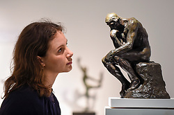 "© Licensed to London News Pictures. 25/06/2019. LONDON, UK. A staff member views ""Le Penseur (The Thinker), Petit Modele"", conceived in 1881-1882, cast by Alexis Rudier between 1920-1930, by Auguste Rodin at Bowman Sculpture at a preview of Masterpiece London 2019, the world's leading cross-collecting art fair held in the grounds of the Royal Hospital Chelsea.  The fair brings together 157 international exhibitors presenting works from antiquity to the present day and runs 27 June to 3 July 2019.  Photo credit: Stephen Chung/LNP"