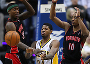 April 09, 2012; Indianapolis, IN, USA; Indiana Pacers shooting guard Paul George (24) dishes the ball off as Toronto Raptors power forward Ed Davis (32) and Toronto Raptors shooting guard DeMar DeRozan (10) defends at Bankers Life Fieldhouse. Mandatory credit: Michael Hickey-US PRESSWIRE