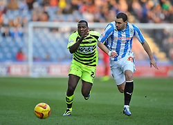 Yeovil Town's Ishmael Miller and Huddersfield Town's Joel Lynch chase down the ball. - Photo mandatory by-line: Alex James/JMP - Tel: Mobile: 07966 386802 29/12/2013 - SPORT - FOOTBALL - John Smith's Stadium - Huddersfield - Huddersfield Town v Yeovil Town - Sky Bet Championship