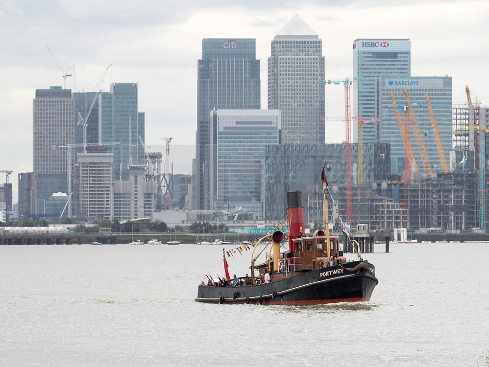 © Licensed to London News Pictures. 04/08/2017. LONDON, UK.  Steam Tug (ST) Portwey steams along the River Thames in front of Canary Wharf skyscrapers in London, travelling to Gravesend to take part in a series of events marking her 90th birthday, including a salute by Commander Richard Pethybridge at the Royal Navy's HMS President on the way. The ST Portwey was built on the Clyde in 1927, came under the command of the Royal Navy during the Second World War when she was based in Dartmouth and carried out rescues of vessels and crews sunk by enemy action in the Channel and is the only twin screw, coal fired steam tug still active in the whole of the United Kingdom.  Photo credit: Vickie Flores/LNP