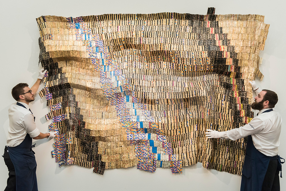 """© Licensed to London News Pictures. 29/03/2019. LONDON, UK. Technicians present """"Zebra Crossing 2"""", 2007, by El Anatsui (Est. GBP 550,000-750,000). Preview of Sotheby's upcoming Modern and Contemporary African Art sale.  Works from artists across the African diaspora will be offered for sale on 2 April.  Photo credit: Stephen Chung/LNP"""