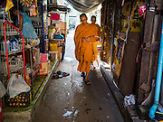 16 OCTOBER 2015 - BANGKOK, THAILAND: Buddhist monks walk through the Wat Kalayanamit neighborhood after their morning alms rounds in Bangkok. Fifty-four homes around Wat Kalayanamit, a historic Buddhist temple on the Chao Phraya River in the Thonburi section of Bangkok, are being razed and the residents evicted to make way for new development at the temple. The abbot of the temple said he was evicting the residents, who have lived on the temple grounds for generations, because their homes are unsafe and because he wants to improve the temple grounds. The evictions are a part of a Bangkok trend, especially along the Chao Phraya River and BTS light rail lines. Low income people are being evicted from their long time homes to make way for urban renewal.    PHOTO BY JACK KURTZ