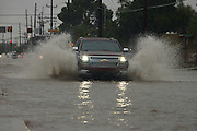 Trucks make their way through flooded streets during a monsoon storm, Sonoran Desert, Tucson, Arizona, USA.
