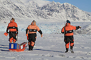 Scienstists walk across frozen fjord ice to collect data about the ice and its role in the carbon cycle; Kongsfjorden, Svalbard, Norway