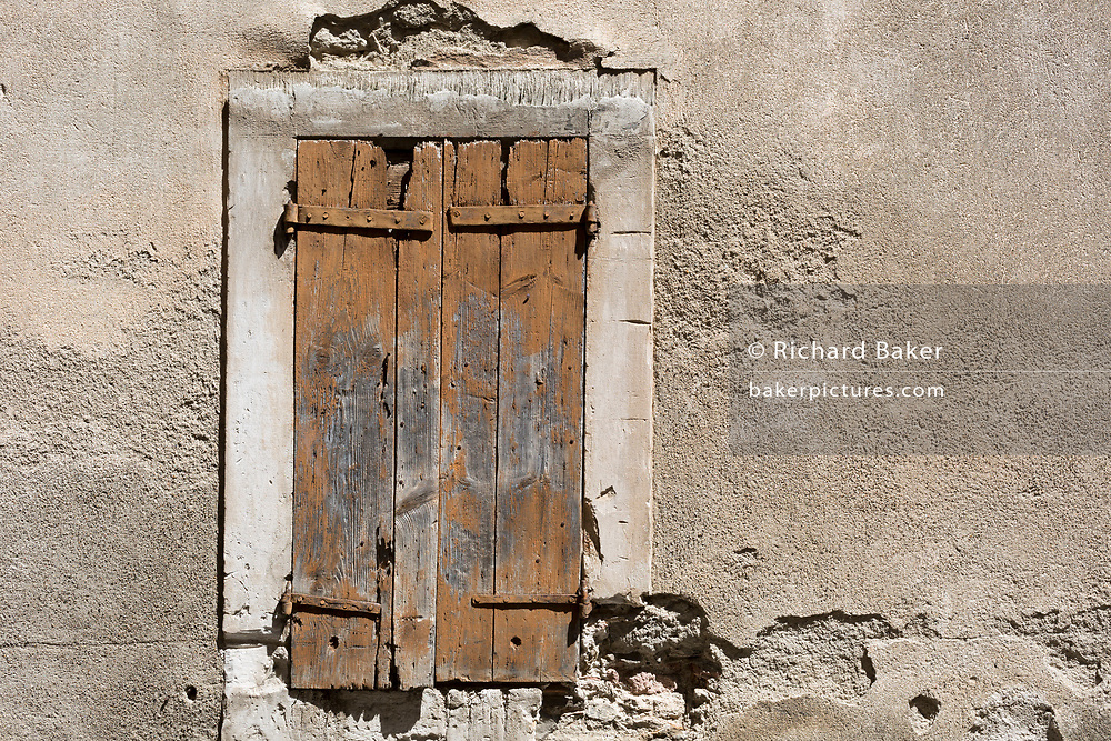 In afternoon heat, baked hard paint textures on village closed wooden shutters, on 25th May, 2017, in Lagrasse, Languedoc-Rousillon, south of France. Lagrasse is listed as one of France's most beautiful villages and lies on the famous Route 20 wine route in the Basses-Corbieres region dating to the 13th century.