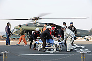 An elderly woman is carried away from a Japan Self Defence Force helicopter after being air-lifted out of Matsushima to the IRed Cross hospital in Ishinomaki, Miyagi Prefecture on 13 March, 2011. Hundreds of people have been evacuated from their homes after a magnitude 9 quake hit northeast Japan on March 11. Photographer: Robert Gilhooly