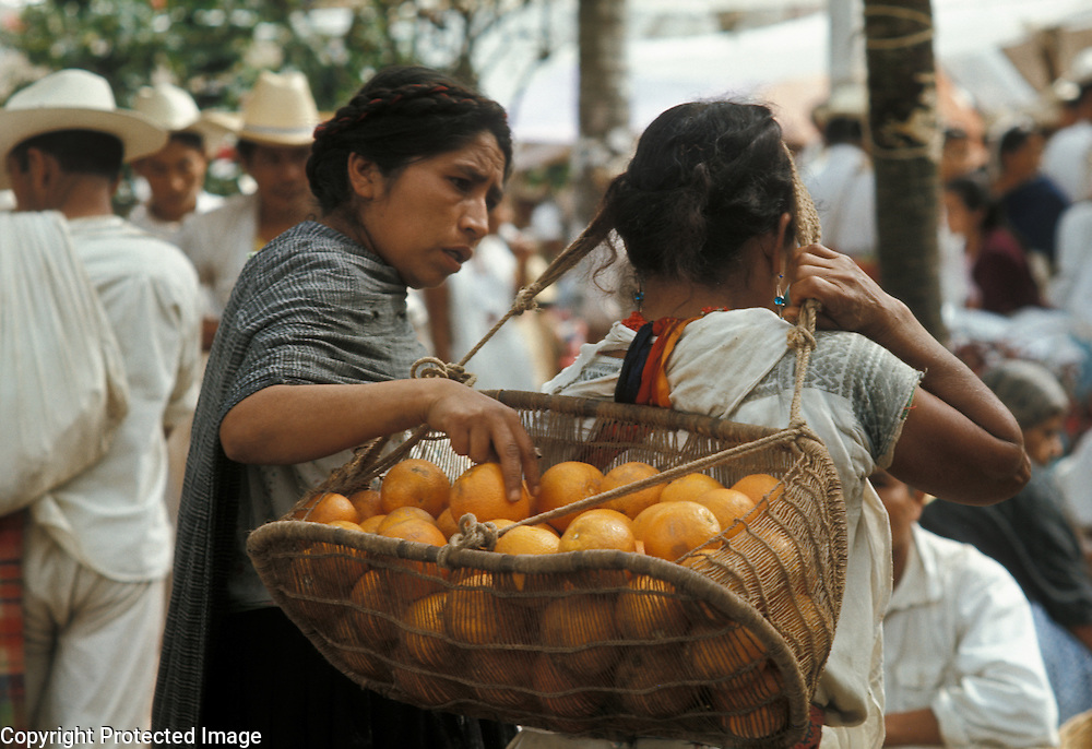 Mexico, Puebla State: Indian woman carrying oranges in basket at Sunday market in small town: Cuetzalan.