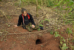 © Licensed to London News Pictures. 08/09/2013.  Gloucestershire, UK.  Campaigner Lynn from Stop the Cull checks near badger setts to see if the cull team have baited them with peanuts to draw the badgers away from the sett entrance so they can be shot. This badger sett looks disused, though there were signs of badgers living there only a few months ago. Lynn fears the badgers may have been killed before the cull began. The Government has licensed a pilot badger cull in parts of Somerset and Gloucestershire as part of efforts to reduce bovine tuberculosis in cows on farms. Campaigners say the cull is inhumane and will not eradicate bovine tuberculosis.  08 September 2013.<br /> Photo credit : Simon Chapman/LNP