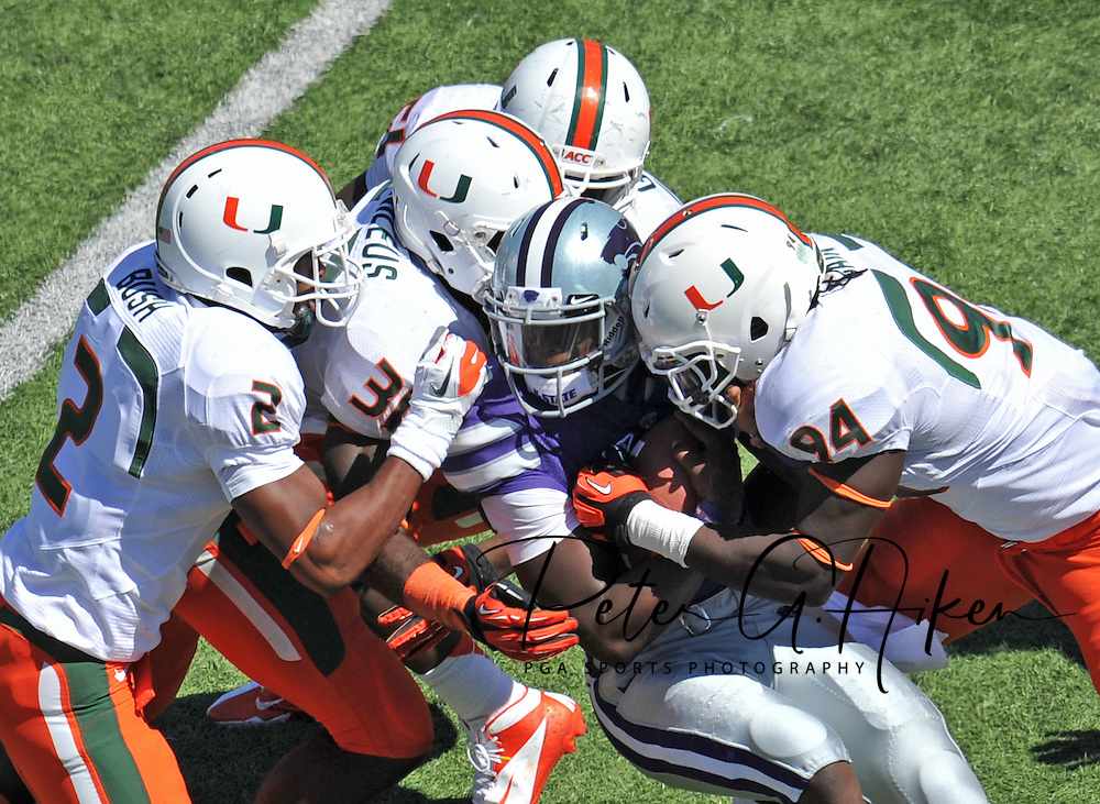 Sports Illustrated -- Defenders Deon Bush #2, Tyrone Cornileus #31 and Kelvin Cain #94 of the Miami Hurricanes tackle quarterback Daniel Sams #4 of the Kansas State Wildcats during the fourth quarter at Bill Snyder Family Stadium in Manhattan, Kansas.  Kansas State defeated Miami 52-13.