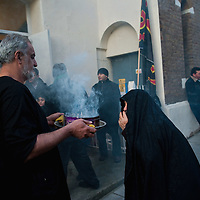 LONDON, ENGLAND - DECEMBER 27:  A Shia Muslim man burns incense as a woman directs the smoke towards herself at the  Ashura procession in front of Holland Park Mosque on December 27, 2009 in London, England. Ashura is a 10 day period of mourning for Imam Hussein, the seven-century grandson of Prophet Mohammad who was killed in a battle in Karbala in Iraq, in 680 AD.  (Photo by Marco Secchi/Getty Images)