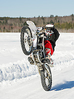 Tyler Sweeney of Lynn, MA pops a wheelie while racing around the plowed track on Lily Pond Saturday morning.  (Karen Bobotas/for the Laconia Daily Sun)