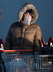 © Licensed to London News Pictures. 31/03/2020. London, UK. A shopper wearing a face mask queues outside Sainsbury's supermarket at Ladbroke Grove in west London. Members of the public have been told they can only leave their homes when absolutely essential, in an attempt to fight the spread of COVID-19, . Photo credit: Ben Cawthra/LNP