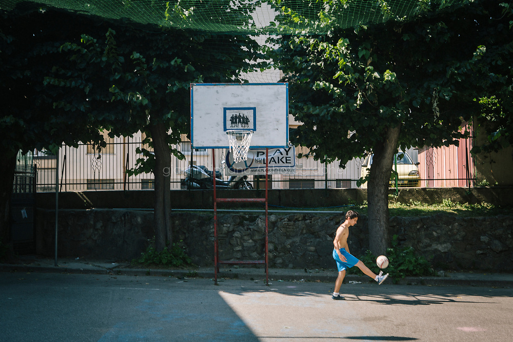 COMO, ITALY - 21 JUNE 2017: A teenager from Kosovo who immigrated to Italy 14 years ago is seen here playing soccer in the playground of the migrant center ran by priest Giusto della Valle in Como, Italy, on June 21st 2017.<br /> <br /> Residents of Como are worried that funds redirected to migrants deprived the town&rsquo;s handicapped of services and complained that any protest prompted accusations of racism.<br /> <br /> Throughout Italy, run-off mayoral elections on Sunday will be considered bellwethers for upcoming national elections and immigration has again emerged as a burning issue.<br /> <br /> Italy has registered more than 70,000 migrants this year, 27 percent more than it did by this time in 2016, when a record 181,000 migrants arrived. Waves of migrants continue to make the perilous, and often fatal, crossing to southern Italy from Africa, South Asia and the Middle East, seeing Italy as the gateway to Europe.<br /> <br /> While migrants spoke of their appreciation of Italy&rsquo;s humanitarian efforts to save them from the Mediterranean Sea, they also expressed exhaustion with the country&rsquo;s intricate web of permits and papers and European rules that required them to stay in the country that first documented them.