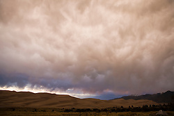 Low hanging storm clouds form over the dune field at sunset.  Great Sand Dunes National Park and Preserve contains the tallest sand dunes in North America. The Dunefield, topping off with Star Dune at 750 feet, is created by sand trapped by the nearby Sangre de Christo Mountains (larger rougher grains and pebbles) and the San Juan Mountains (65 miles to the west).  Waterways such as Medano Creek help carry the sediment down to the San Luis valley where the dunes are found. Great Sand Dunes National Park and Preserve, Mosca, Colorado.