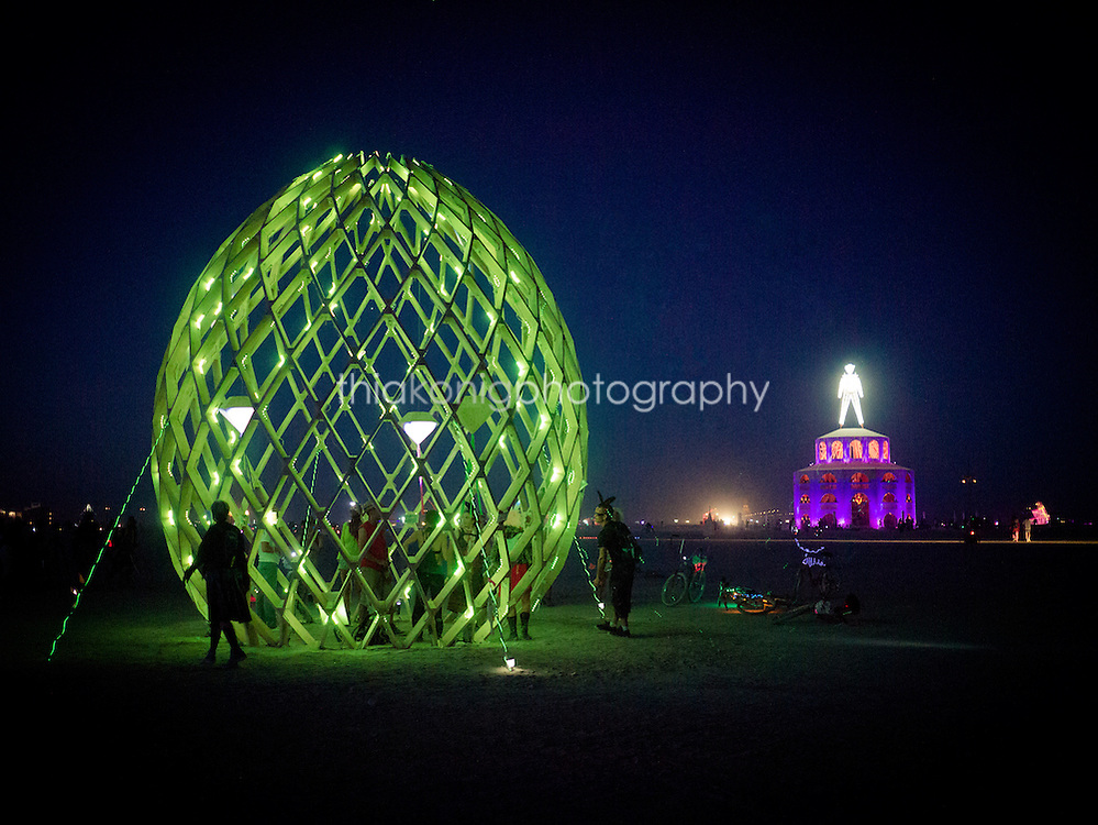 Green neon egg shaped art installation with 'the man' in the background, Black Rock City, Burning Man Festival.