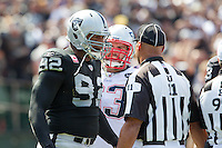 02 October 2011: Defensive tackle (92) Richard Seymour of the Oakland Raiders argues with NFL Umpire (11) Fred Bryan after throwing Tom Brady down after the whistle and being penalized while playing the New England Patriots during the first half of the Patriots 31-19 victory against the Raiders in an NFL football game at O.co Stadium in Oakland, CA.