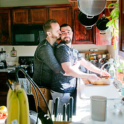 Shadi Ismail (middle, at sink) gets a kiss from boyfriend Ian Guthrie (left) while washing dishes in their home in Boise, Idaho. Shadi, a Syrian refugee says about his new life in Boise, &quot;I didn't think I would be alive&quot; (to experience life in the United States). &quot;I wish everyone had what we have. We are very happy. We are in a very good spot in our lives&quot;, Shadi added about this relationship with boyfriend Ian.<br /> Despite resistance by Idaho&rsquo;s top political leaders, 108 Syrian refugees have moved to the Gem State since Oct. 1, with all of them settling in Boise, according to new data from the U.S. State Department. Compared to larger cities, Boise took in a disproportionate share, accepting exactly twice as many refugees as New York, with 9, and Los Angeles, with 45, combined. In Boise, no one&rsquo;s more excited to welcome the newcomers than Shadi Ismail, 29, one of the first Syrian refugees wh o moved to the city in 2012. &ldquo;It&rsquo;s good, very good news --- people coming in, being safe now,&rdquo; Ismail said.  &ldquo;They will have life.&rdquo; In Syria, Ismail feared his family would kill him for being gay, fleeing after his father and brother burned him with charcoal in an attempt to rid him of his homosexuality. Friday September 9, 2016