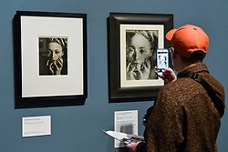 "© Licensed to London News Pictures. 19/11/2019. LONDON, UK. A visitor views ""The Years Lie in Wait For You"", c1935, and ""Untitled (Nusch Eluard)"", c1945, by Dora Maar. Preview of the first UK retrospective of Dora Maar (born Henriette Theodora Markovitch, 1907-97) whose photographs and photomontages became celebrated icons of surrealism.  Over 200 of her works are on display in a career spanning more than six decades at Tate Modern 20 November to 15 March 2020.  Photo credit: Stephen Chung/LNP"