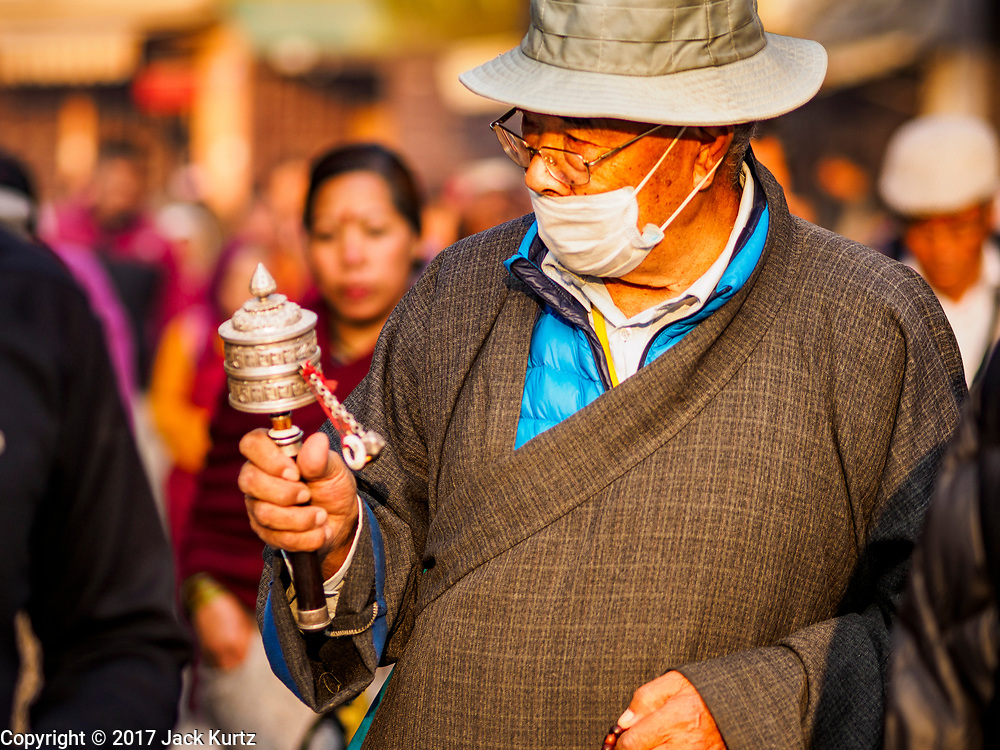 17 MARCH 2017 - KATHMANDU, NEPAL: A man prays as he walks around Boudhanath Stupa in Kathmandu during morning prayers. The stupa is the holiest site in Nepali Buddhism. It is also the center of the Tibetan exile community in Kathmandu. The Stupa was badly damaged in the 2015 earthquake but was one of the first buildings renovated.     PHOTO BY JACK KURTZ