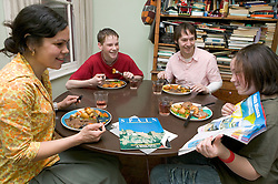 Family having lunch at home talking about where to go for a Summer holiday,