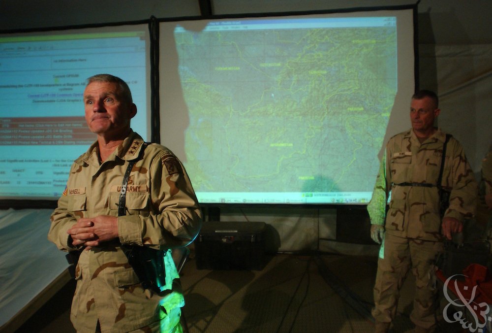 """U.S. Army General Dan McNeill, Coalition Joint Task Force (CJTF) 180 commander (l), speaks to the news media inside the recently constructed CJTF-180 Joint Operations Center May 29, 2002 at Bagram airbase in Afghanistan. As of May 31, 2002, the high-tech operations center will control all U.S. and coalition forces in the Afghan theater of operation via a secure high speed """"secret"""" Internet network under McNeill's command."""