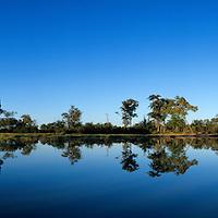 Africa, Botswana, Chobe National Park, Rising sun lights pond at Sarigho Pan near Nogatsaa on winter morning