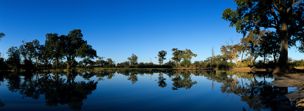 Africa, Botswana, Chobe National Park, Rising sun lights pond at Sarigho Pan near Nogatsaa on winter morning
